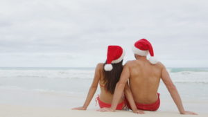 man and woman on beach in santa hats